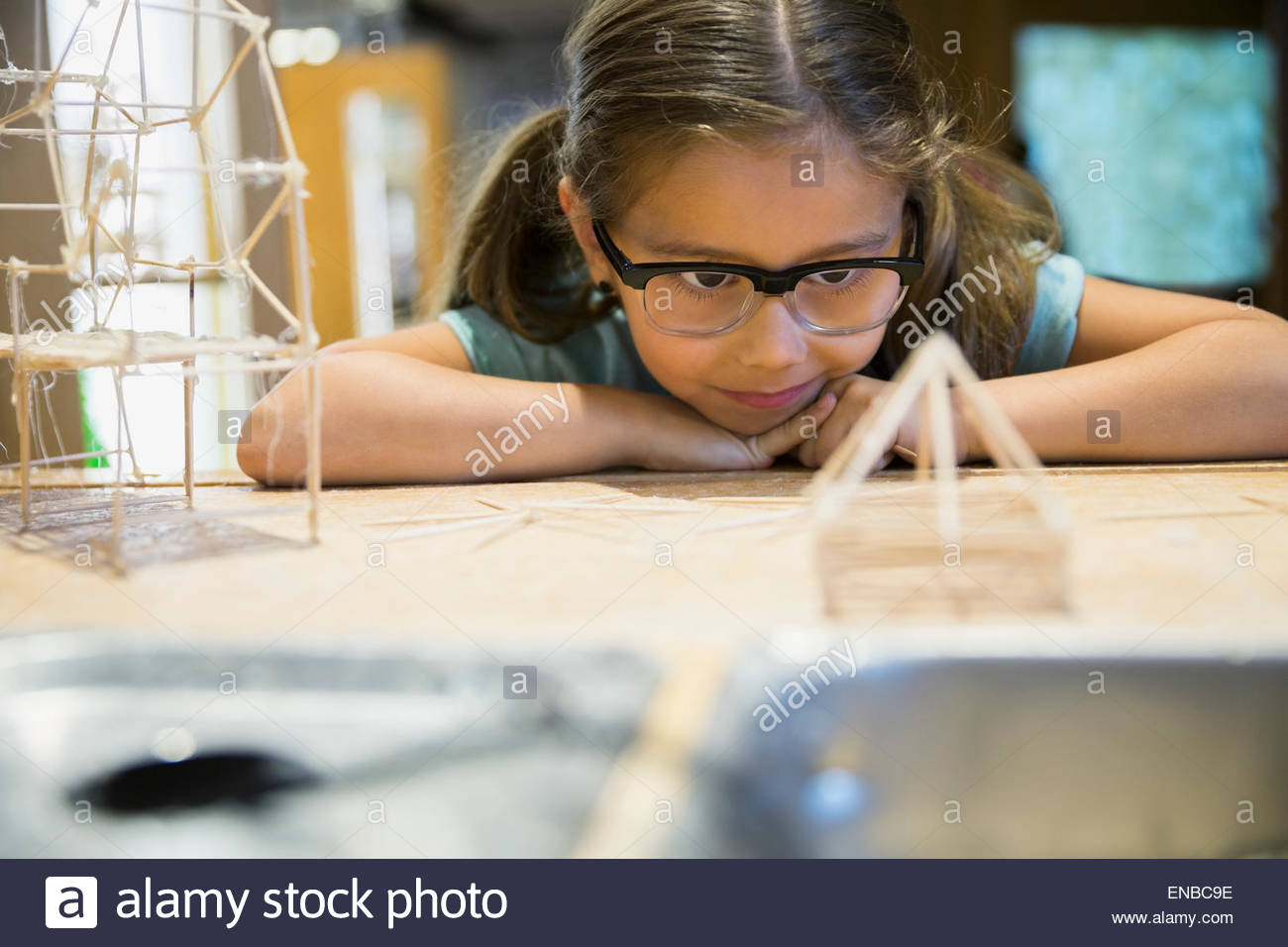 Girl examining toothpick model at science center - Stock Image