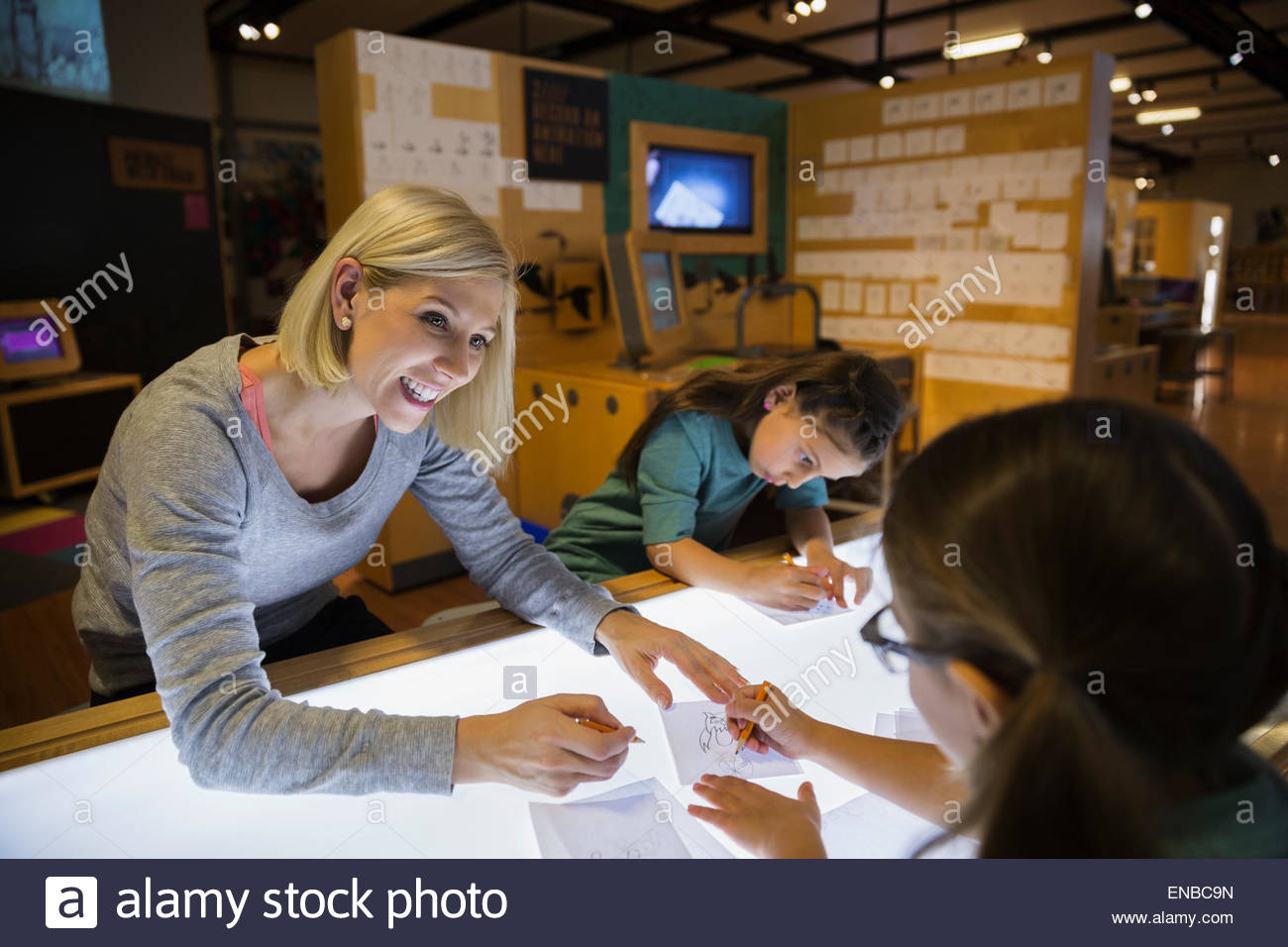 Family tracing on light table at science center - Stock Image
