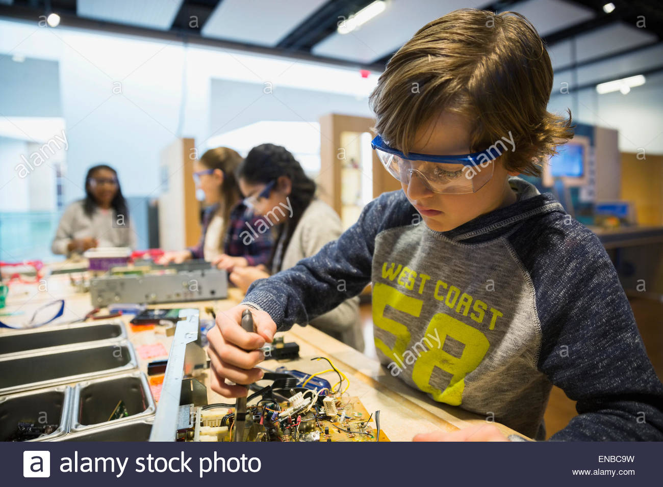 Curious boy assembling electronic circuit at science center - Stock Image
