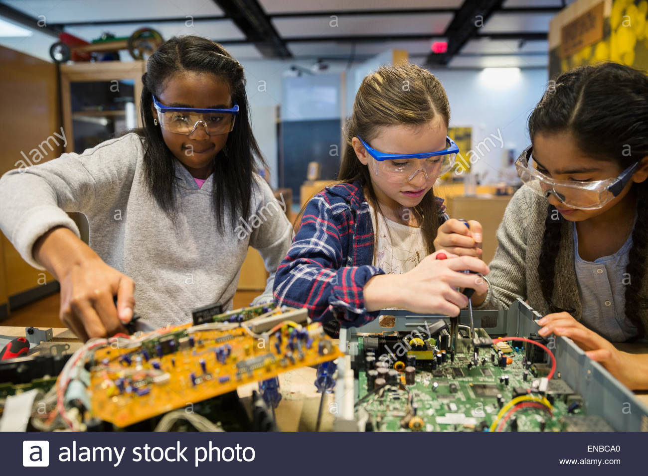 Students in goggles assembling electronics at science center - Stock Image