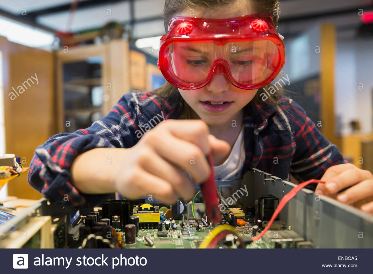 Girl goggles assembling electronics circuit at science center - Stock Image
