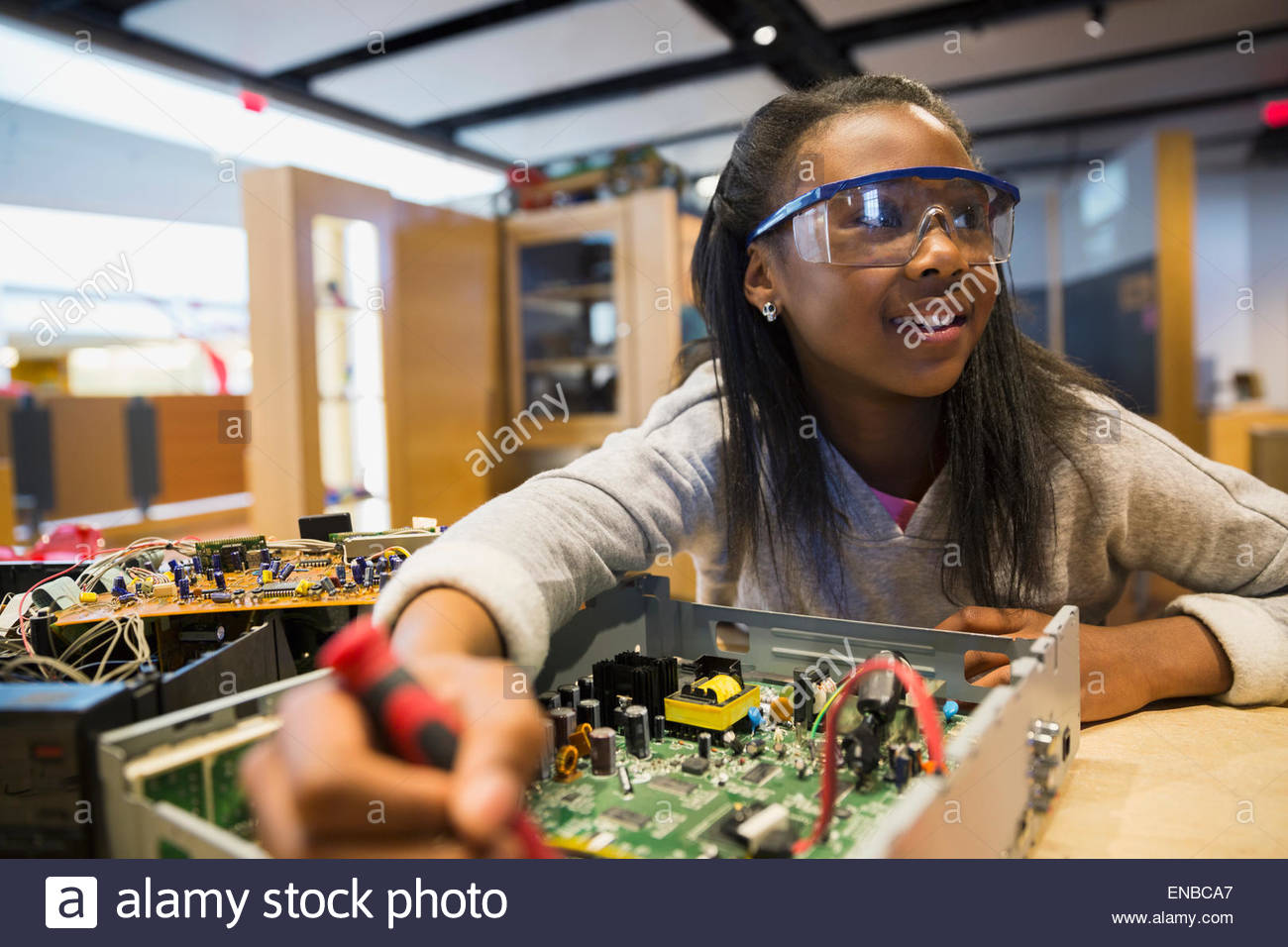 Girl goggles assembling electronics circuit at science center Stock Photo