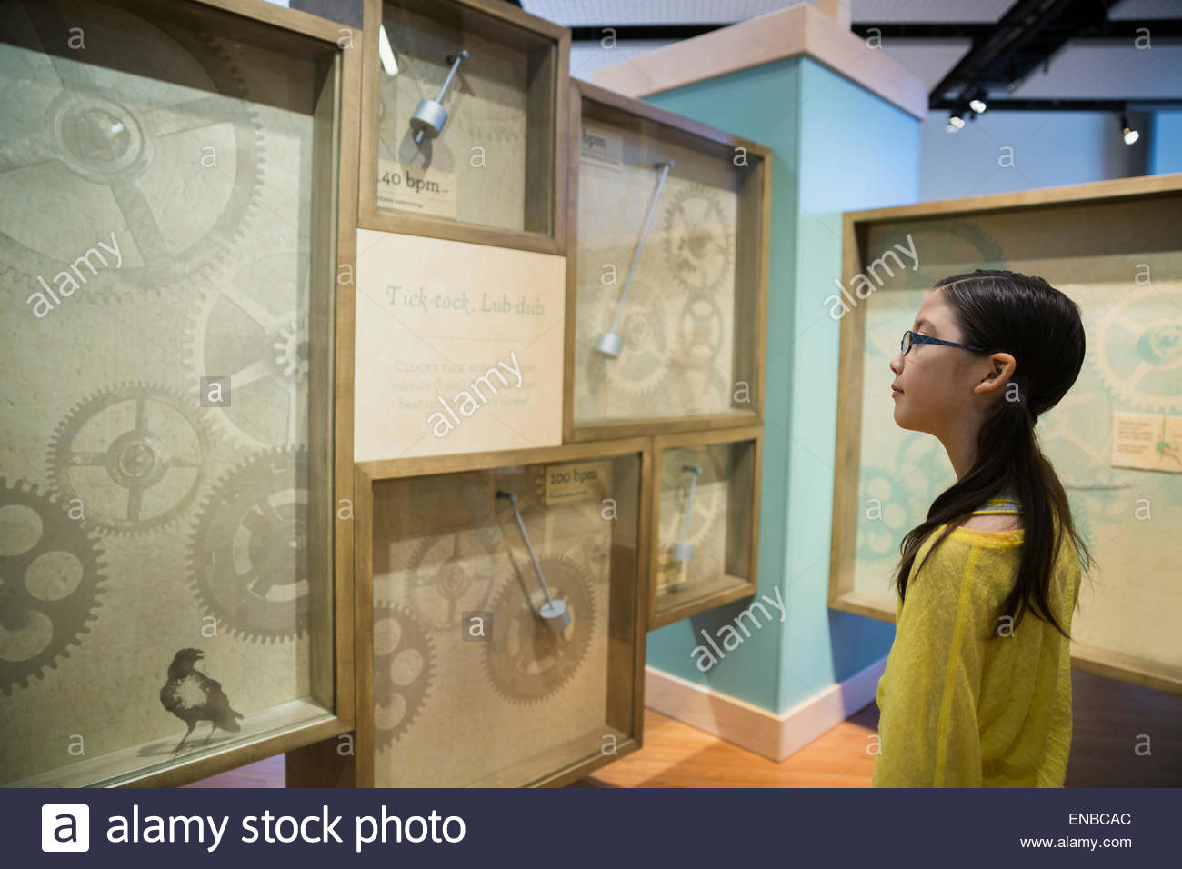 Curious girl viewing clock exhibit at science center - Stock Image