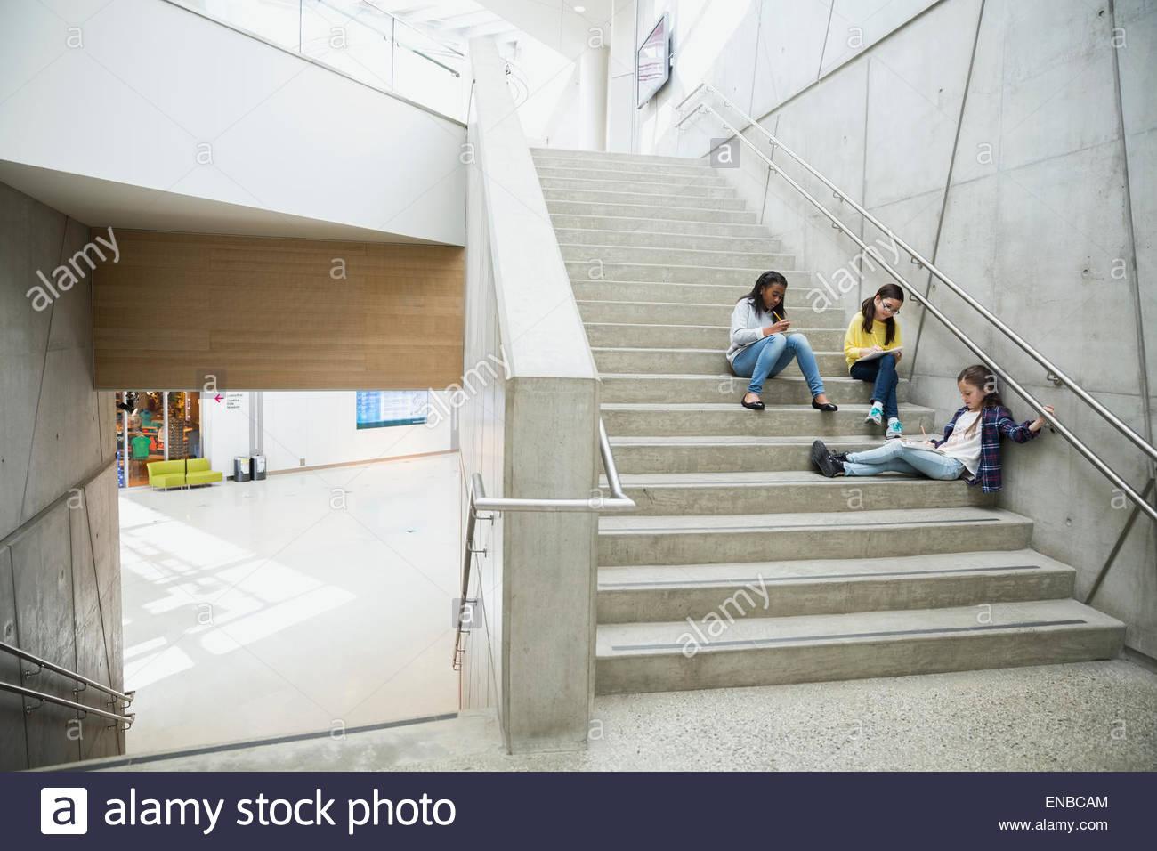 Schoolgirls Doing Homework On Stairs Outside   Stock Image