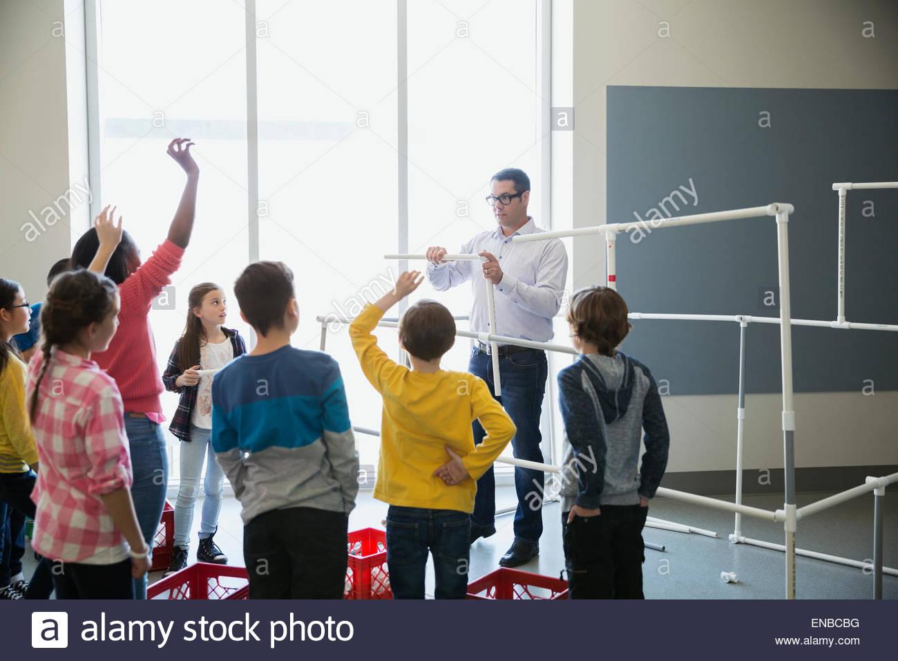 Teacher and students assembling model pipeline - Stock Image