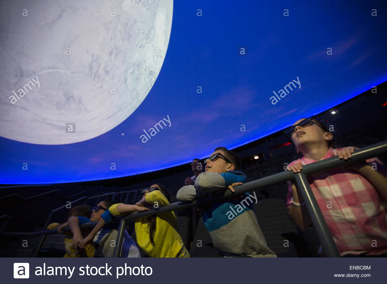 Curious students watching moon in planetarium show - Stock Image
