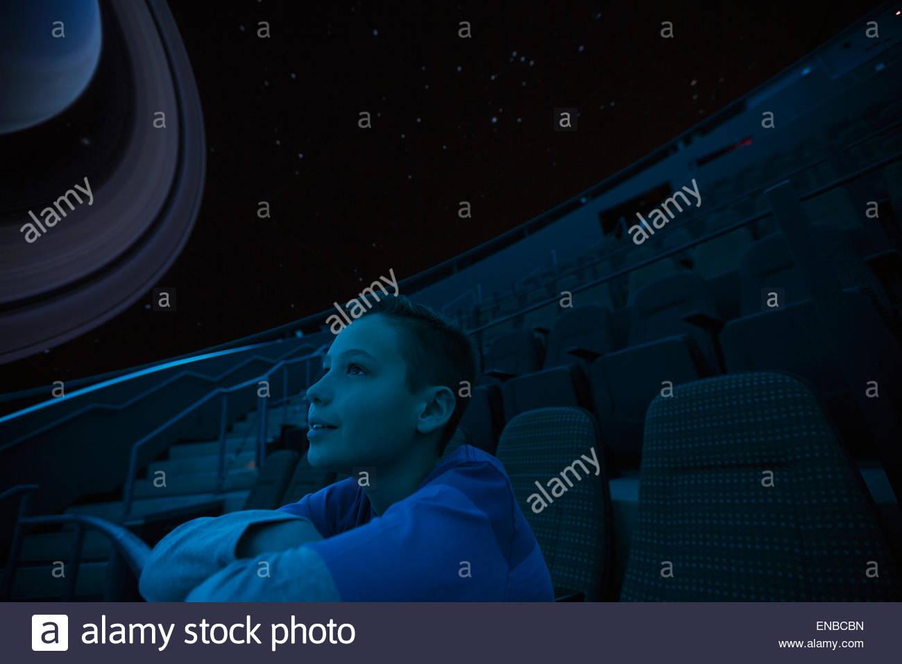 Curious boy enjoying planetarium show - Stock Image