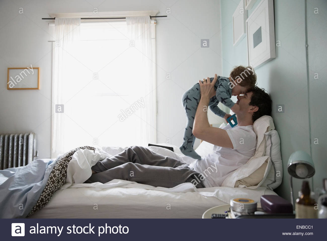 Father and son in pajamas cuddling in bed - Stock Image