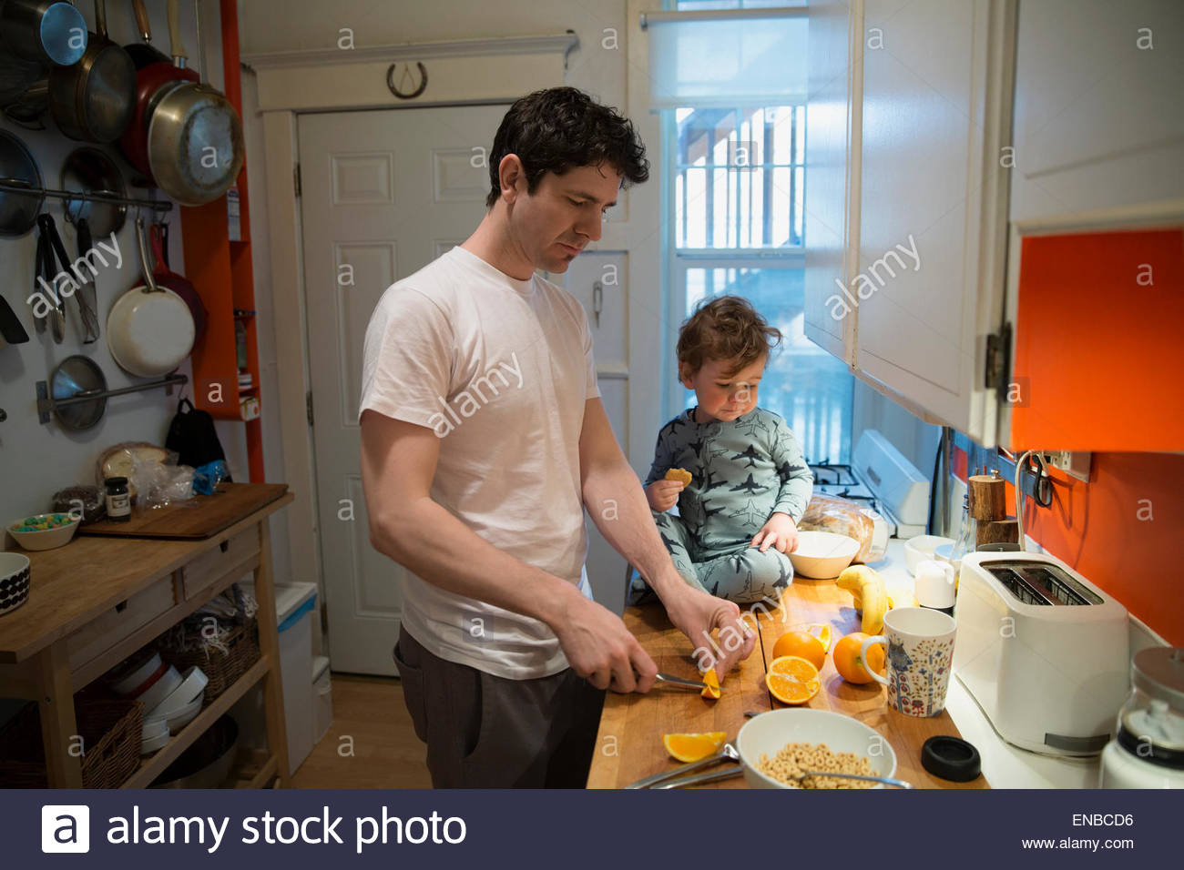 Father and son cutting oranges for breakfast kitchen - Stock Image