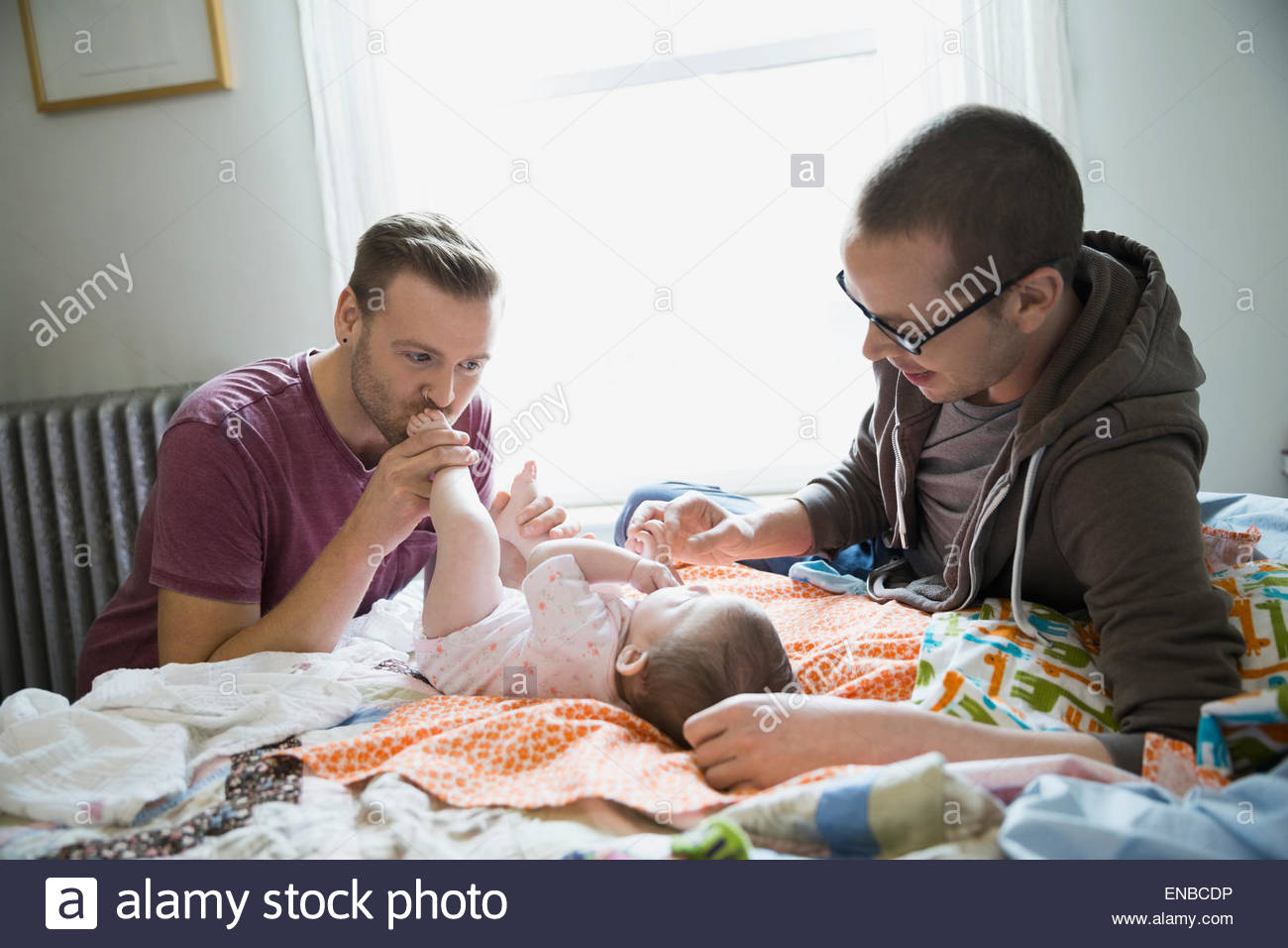 Homosexual couple playing with baby on bed - Stock Image