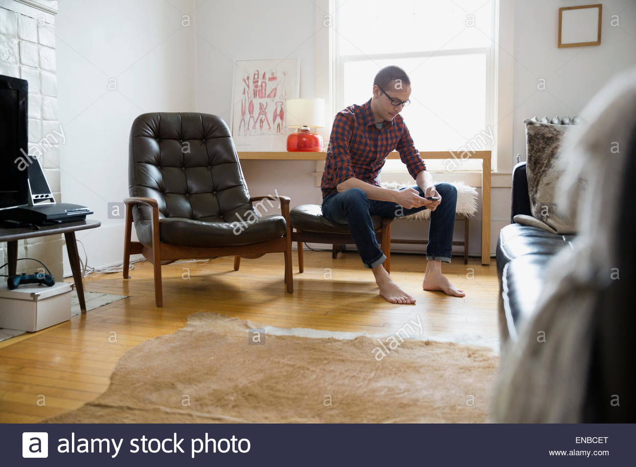 Barefoot man texting with cell phone living room - Stock Image