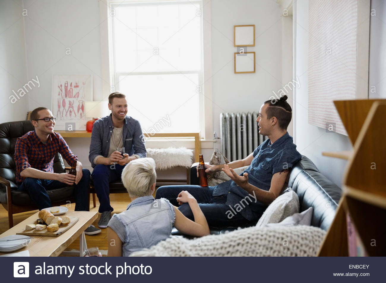 Homosexual and heterosexual couples hanging out living room - Stock Image