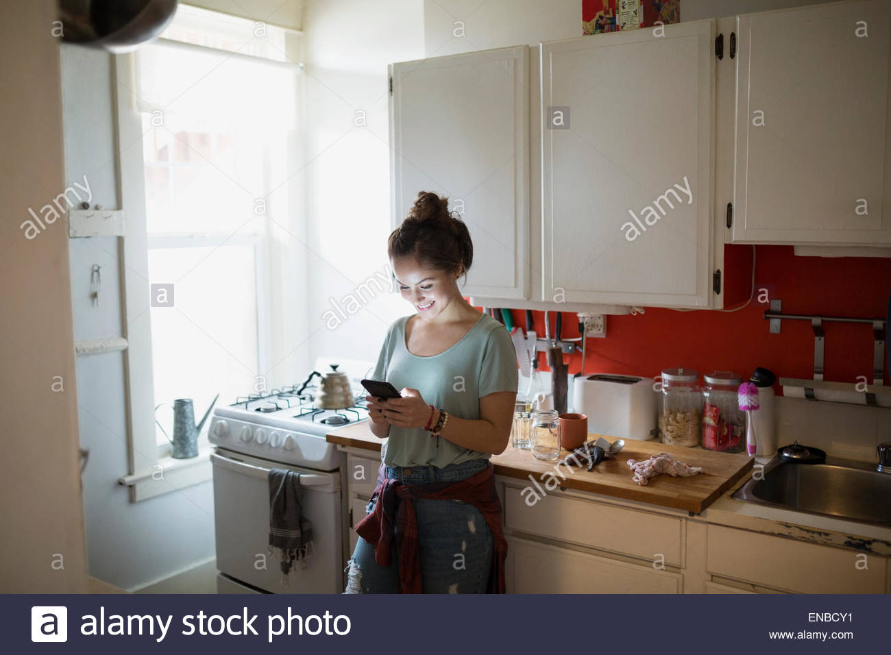 Smiling woman texting with cell phone in kitchen - Stock Image