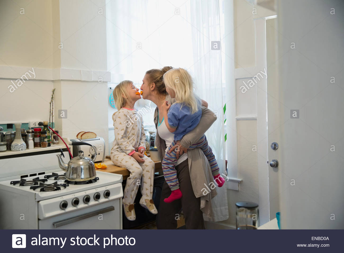 Playful mother and daughters in morning kitchen - Stock Image