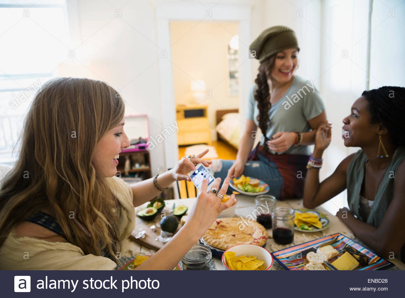 Woman photographing food with camera phone dining table - Stock Image