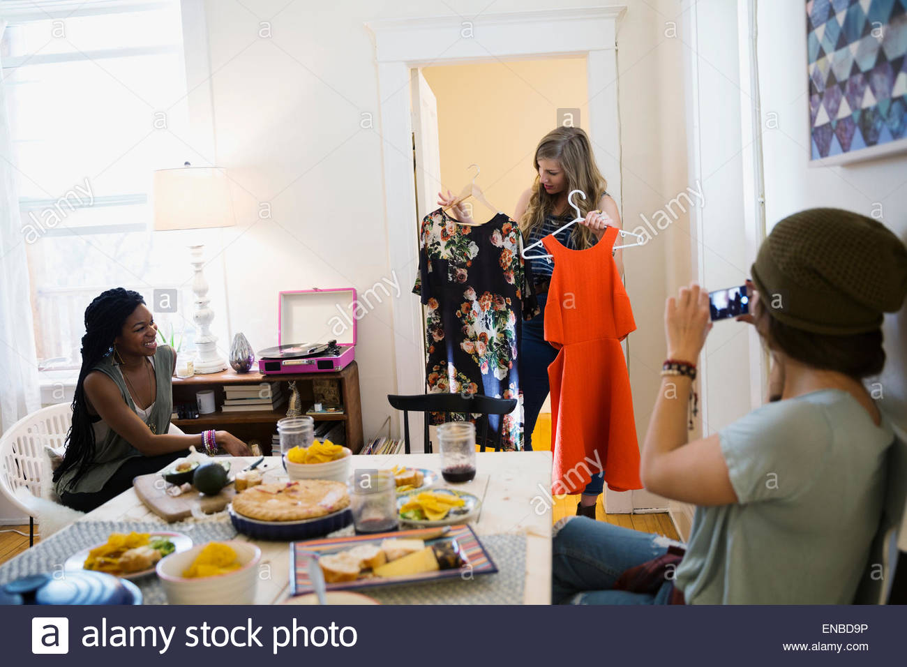 Woman showing dress choices to friends - Stock Image