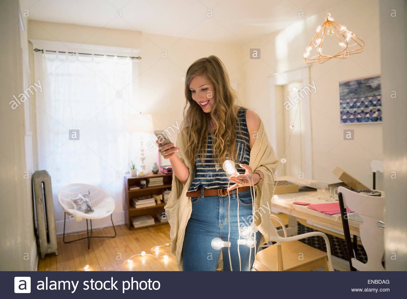 Woman with string lights texting with cell phone Stock Photo