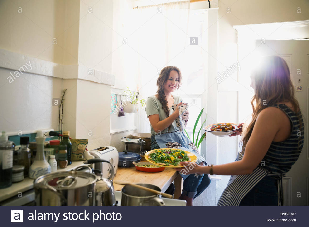 Friends cooking and talking in sunny kitchen - Stock Image