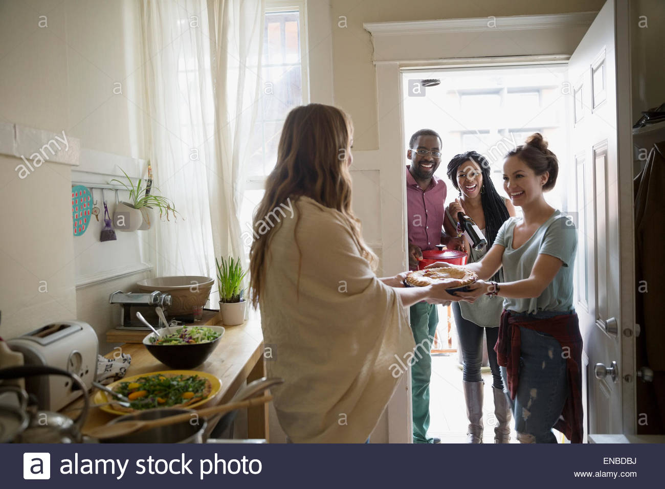 Woman greeting friends arriving for potluck dinner party - Stock Image