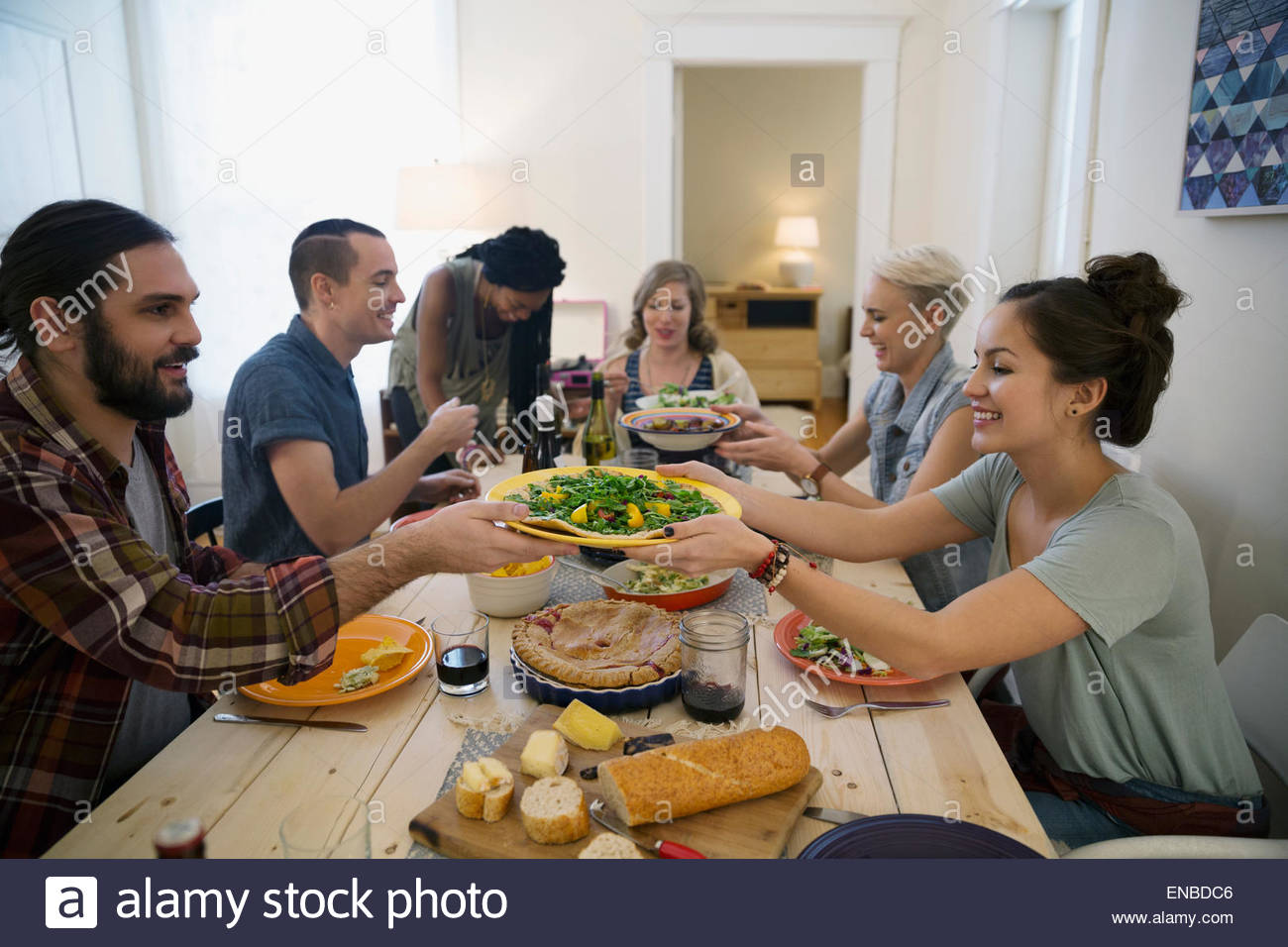 Friends passing food at dinner party - Stock Image