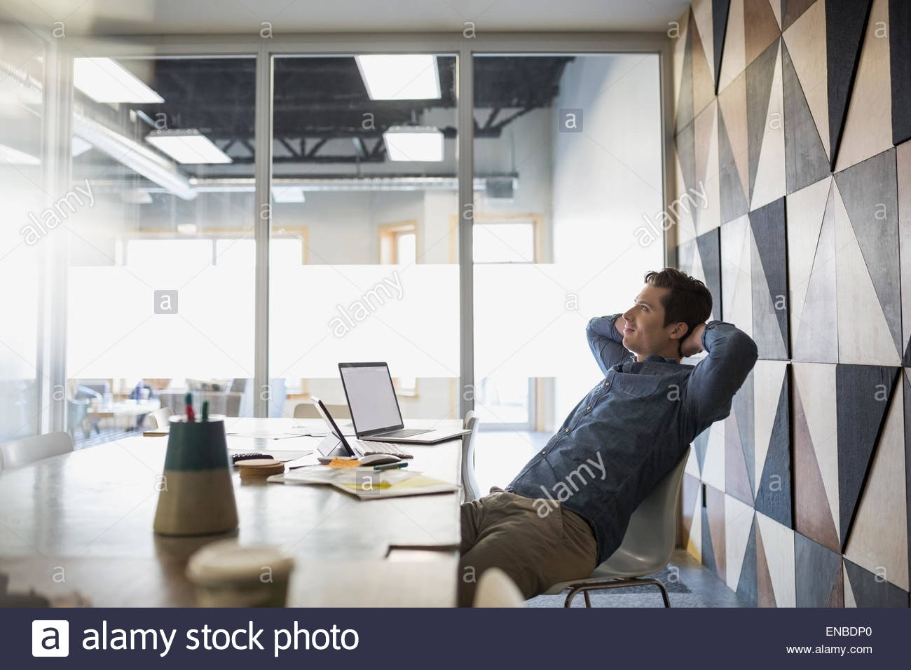 Casual businessman relaxing hands behind head conference room - Stock Image