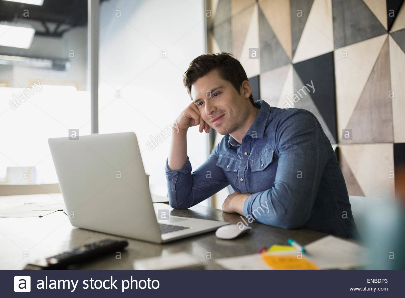 Casual businessman working at laptop in conference room - Stock Image