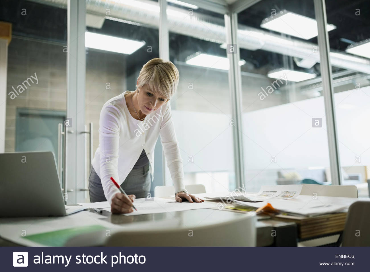 Businesswoman editing proofs in conference room - Stock Image