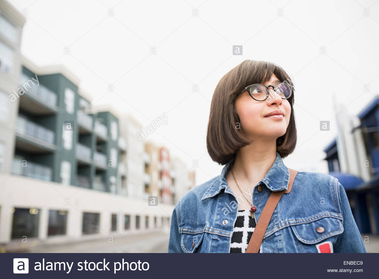 Woman in denim jacket on urban street - Stock Image