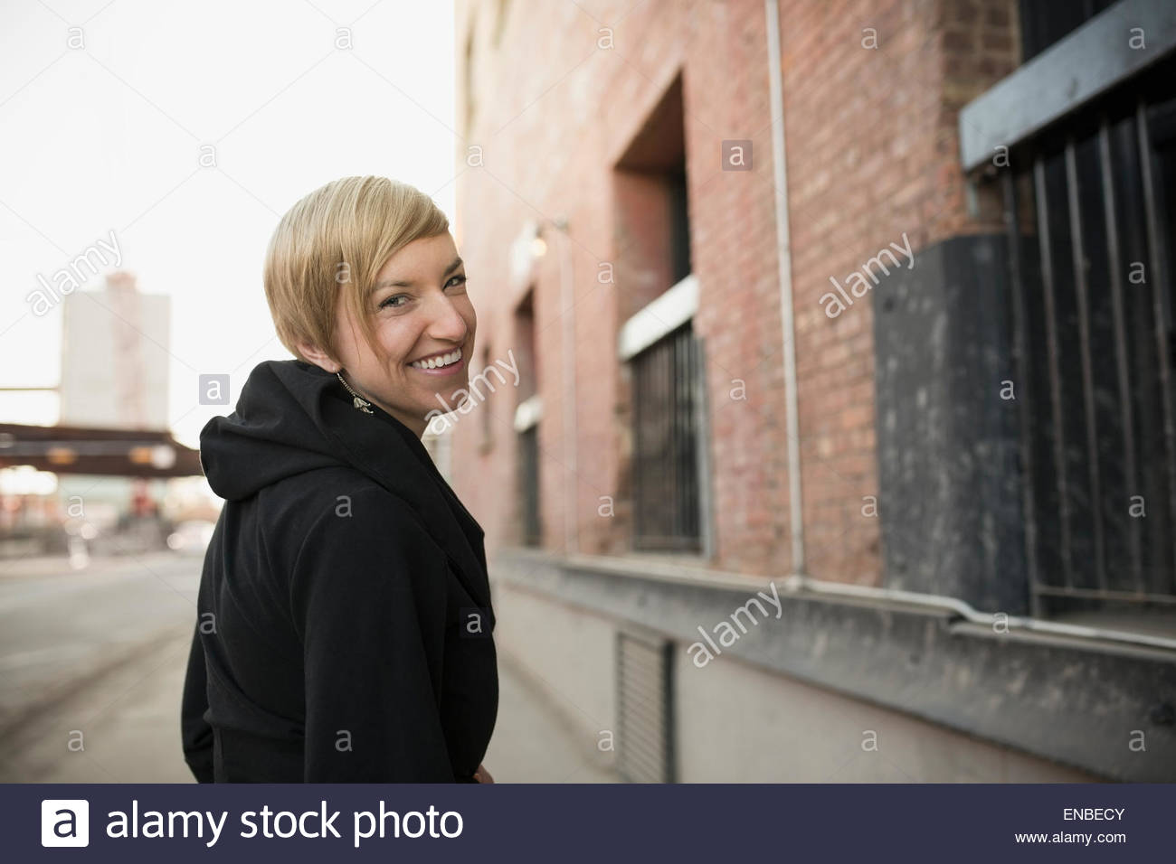 Portrait of smiling blonde woman turning on urban street - Stock Image