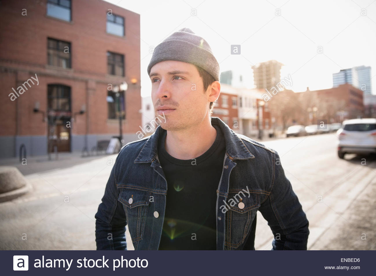 Serious man looking away denim jacket urban street - Stock Image