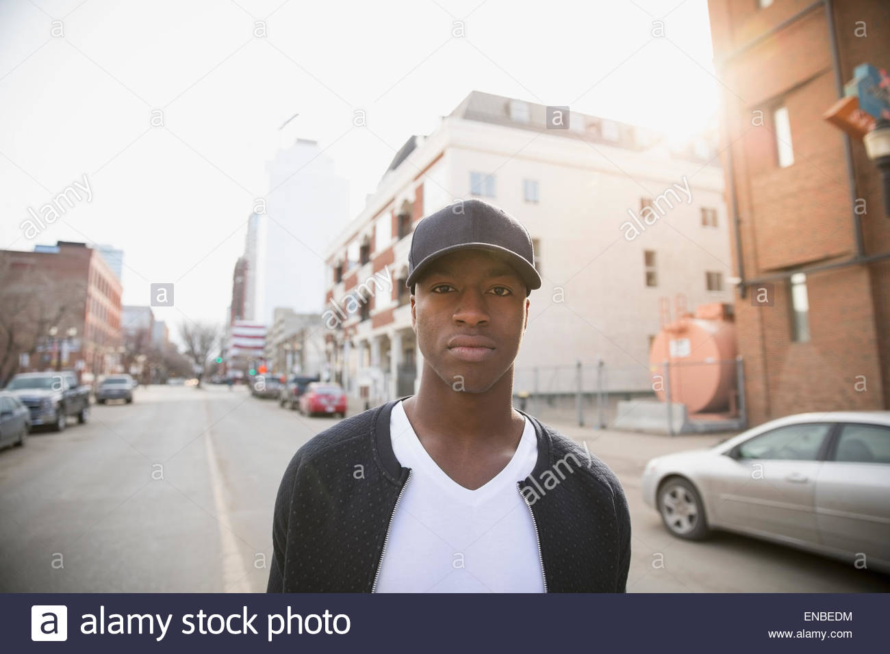 Portrait serious man in baseball cap urban street - Stock Image