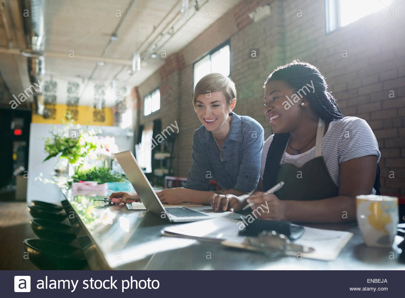 Florists working at laptop in sunny flower shop - Stock Image
