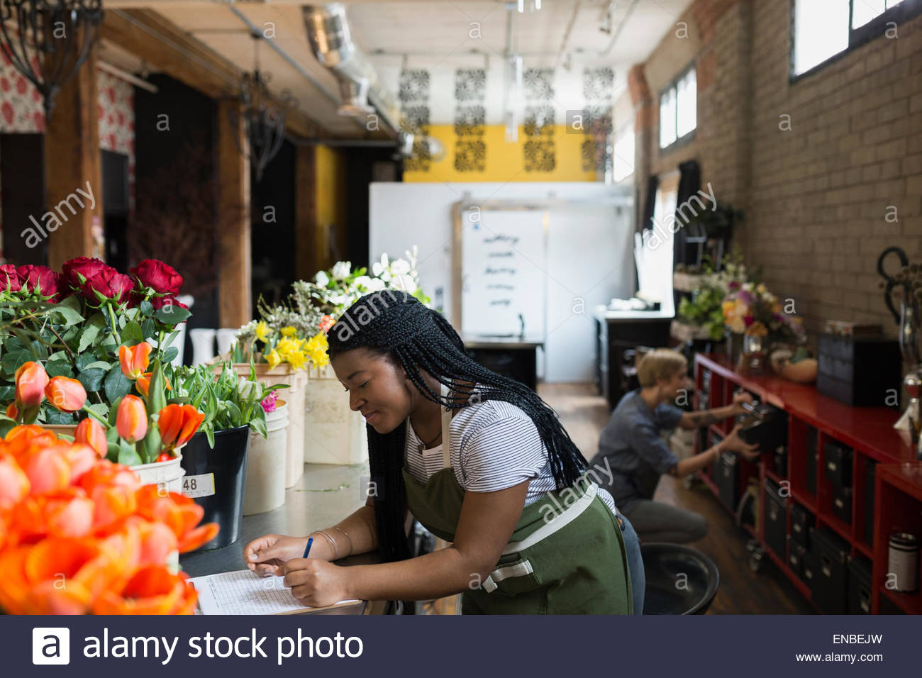 Florist with clipboard checking flower inventory flower shop - Stock Image