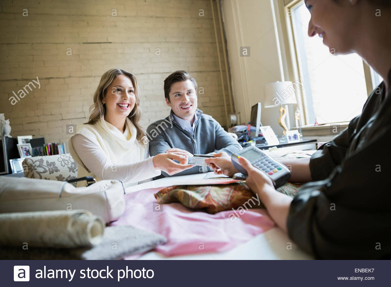 Couple paying interior designer with credit card - Stock Image