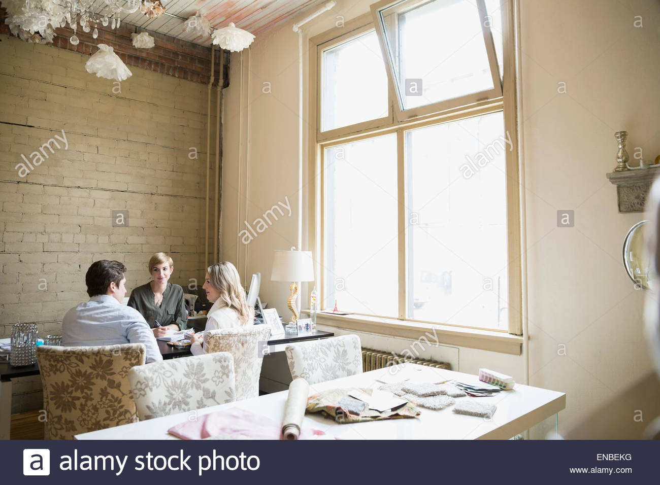 Couple in consultation with interior designer in office - Stock Image