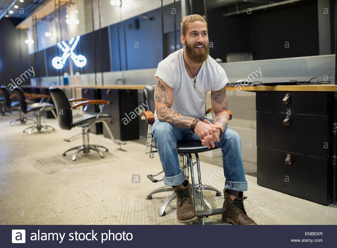 Hipster hairstylist sitting in hair salon - Stock Image