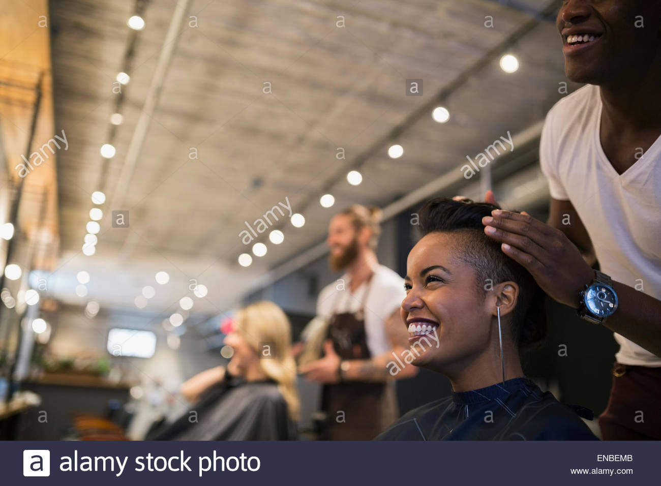 Smiling woman getting hair styled in hair salon - Stock Image