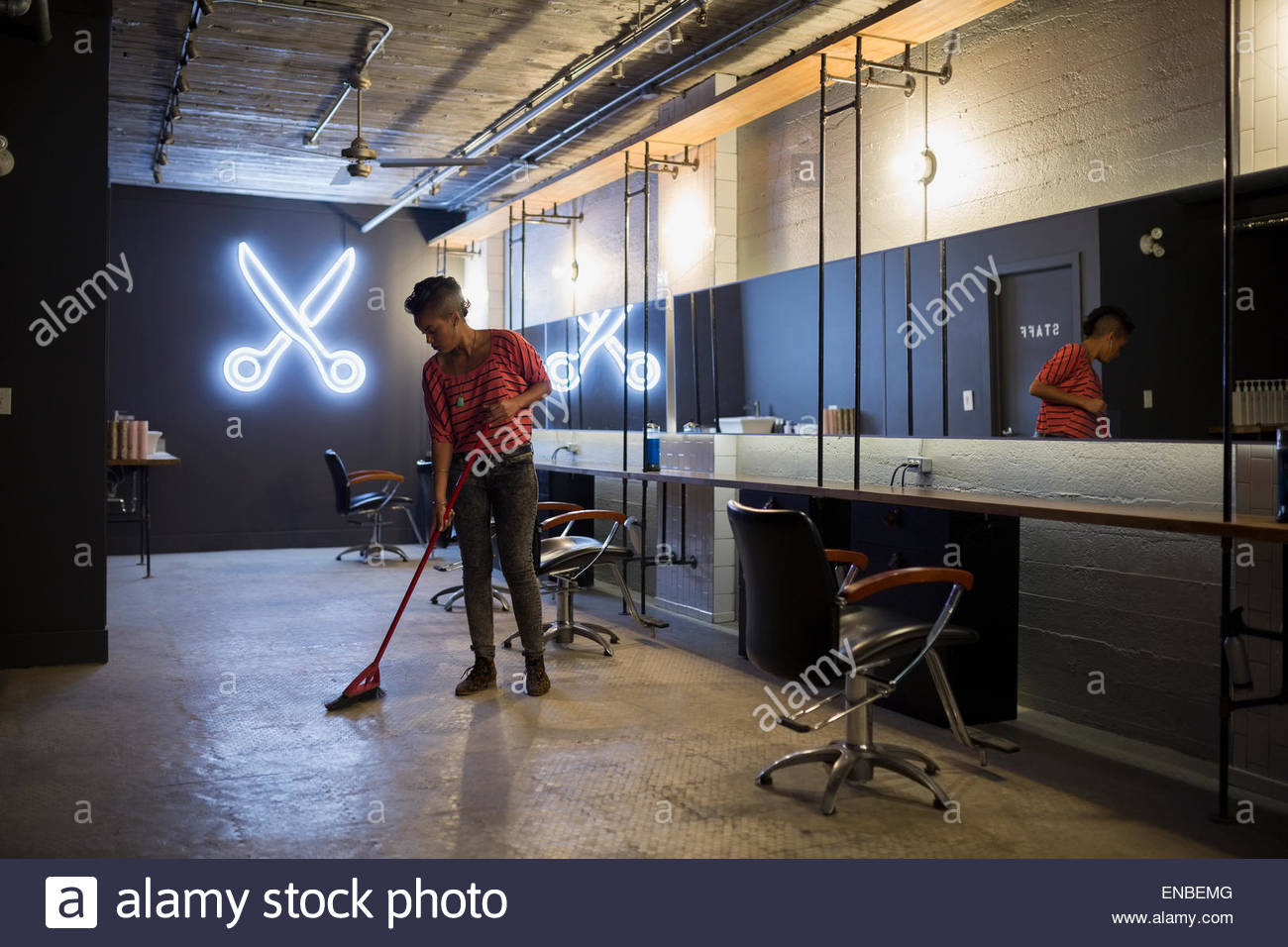 Hairstylist sweeping hair salon floor with broom - Stock Image