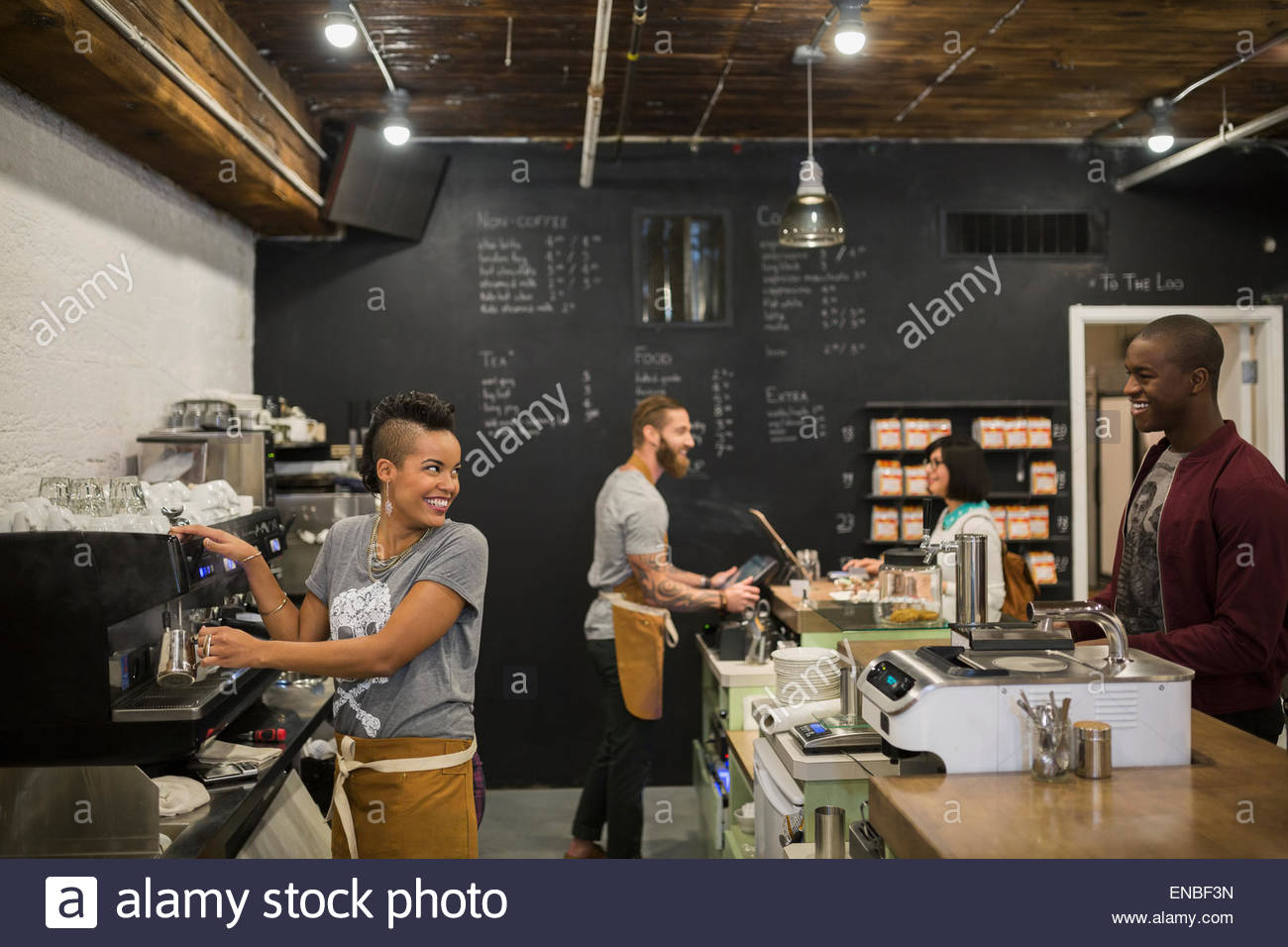 Baristas serving customers in coffee shop - Stock Image