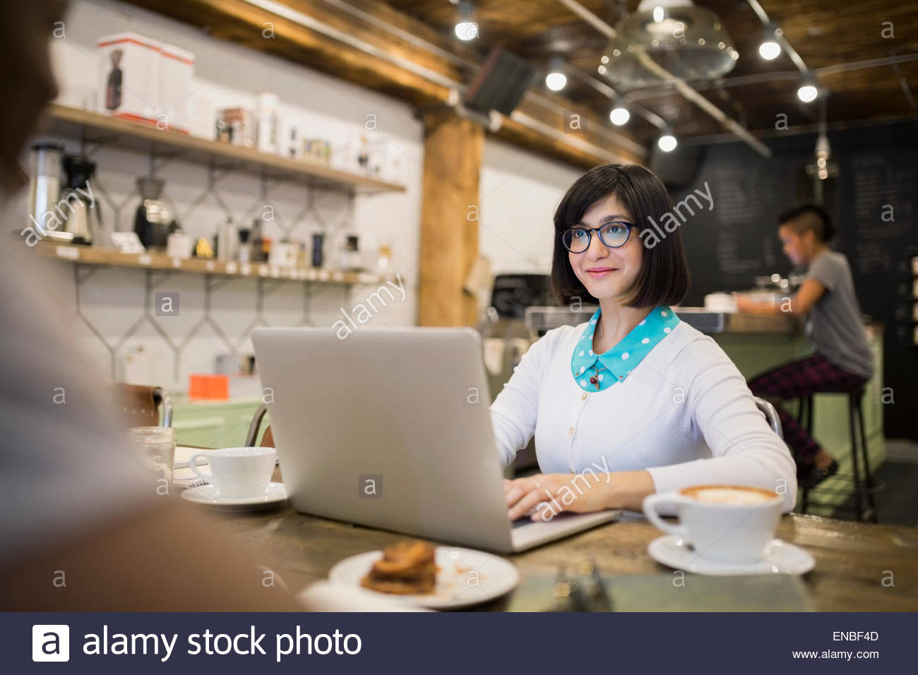 Woman working at laptop in cafe - Stock Image