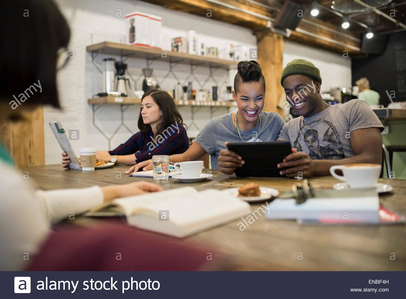 Smiling couple sharing digital tablet in cafe - Stock Image
