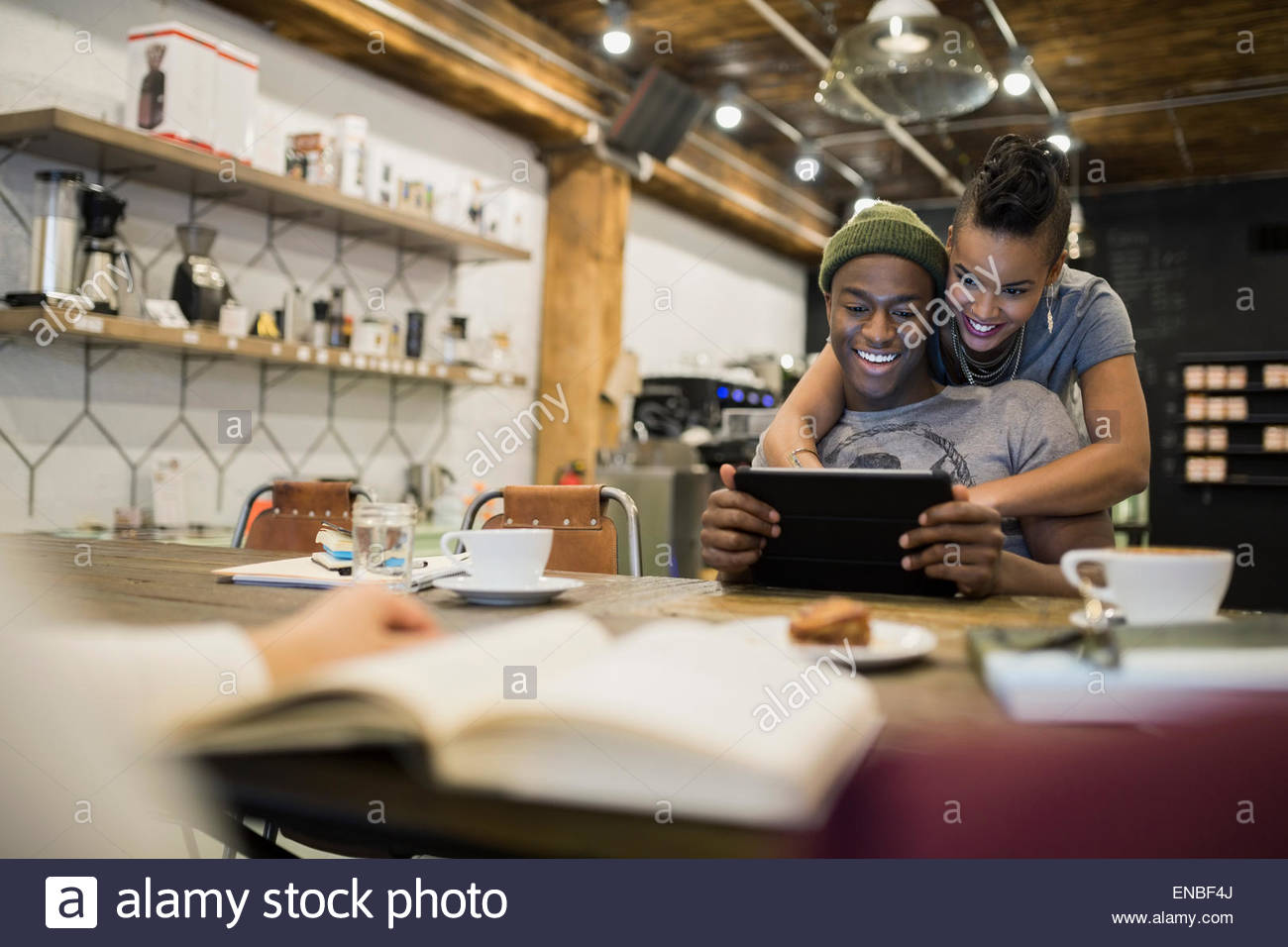 Smiling couple using digital tablet in cafe Stock Photo