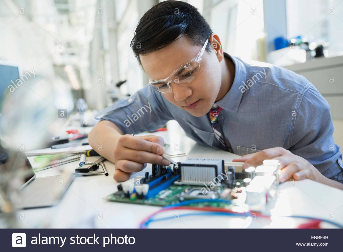 Focused engineer assembling circuit board - Stock Image