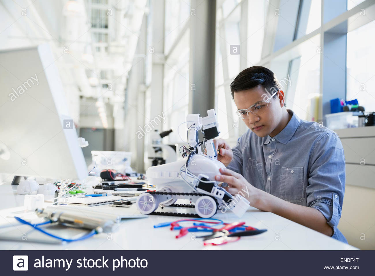 Focused engineer assembling robotic car - Stock Image