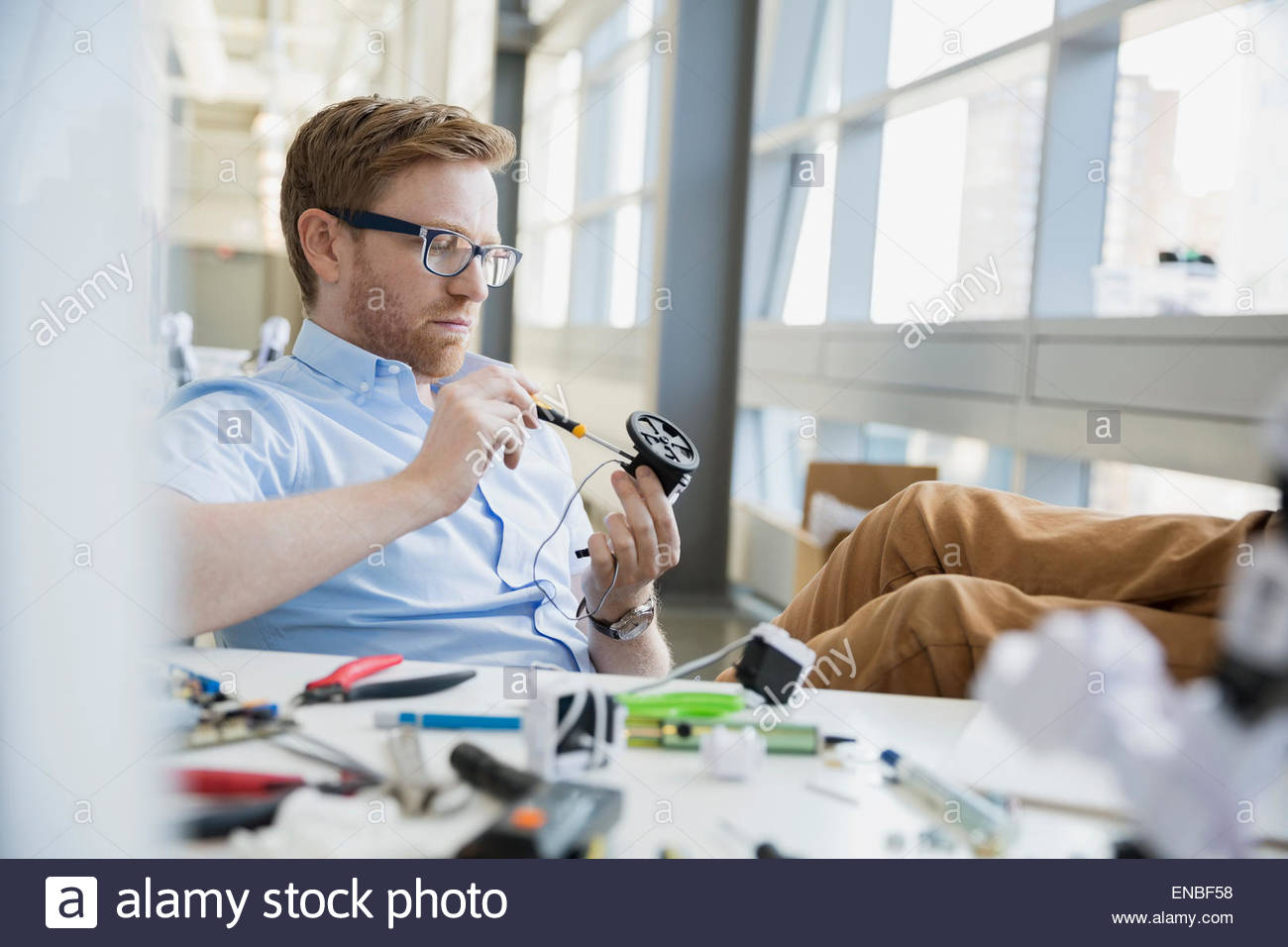 Engineer assembling robotics at desk with feet up - Stock Image
