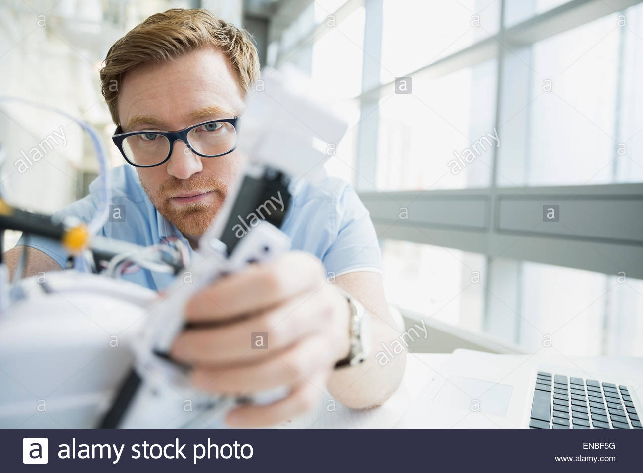 Focused engineer examining robot - Stock Image