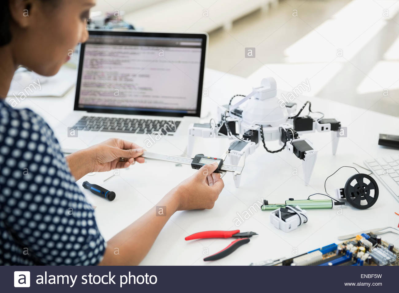 Engineer measuring robot with calipers - Stock Image