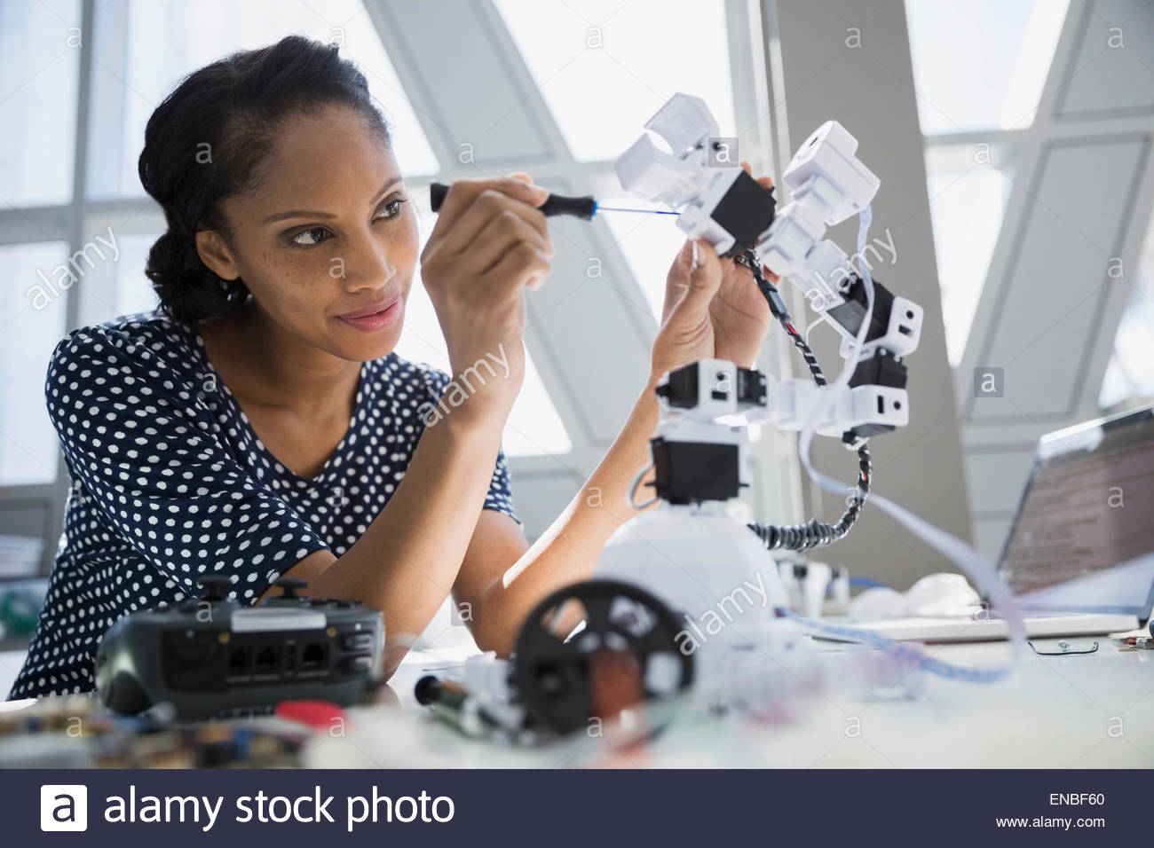 Engineer assembling robotic arm at desk - Stock Image