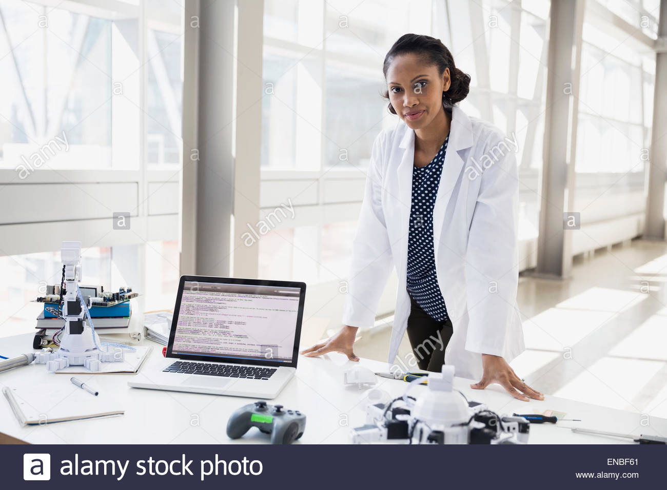 Portrait of confident engineer at desk with robots Stock Photo