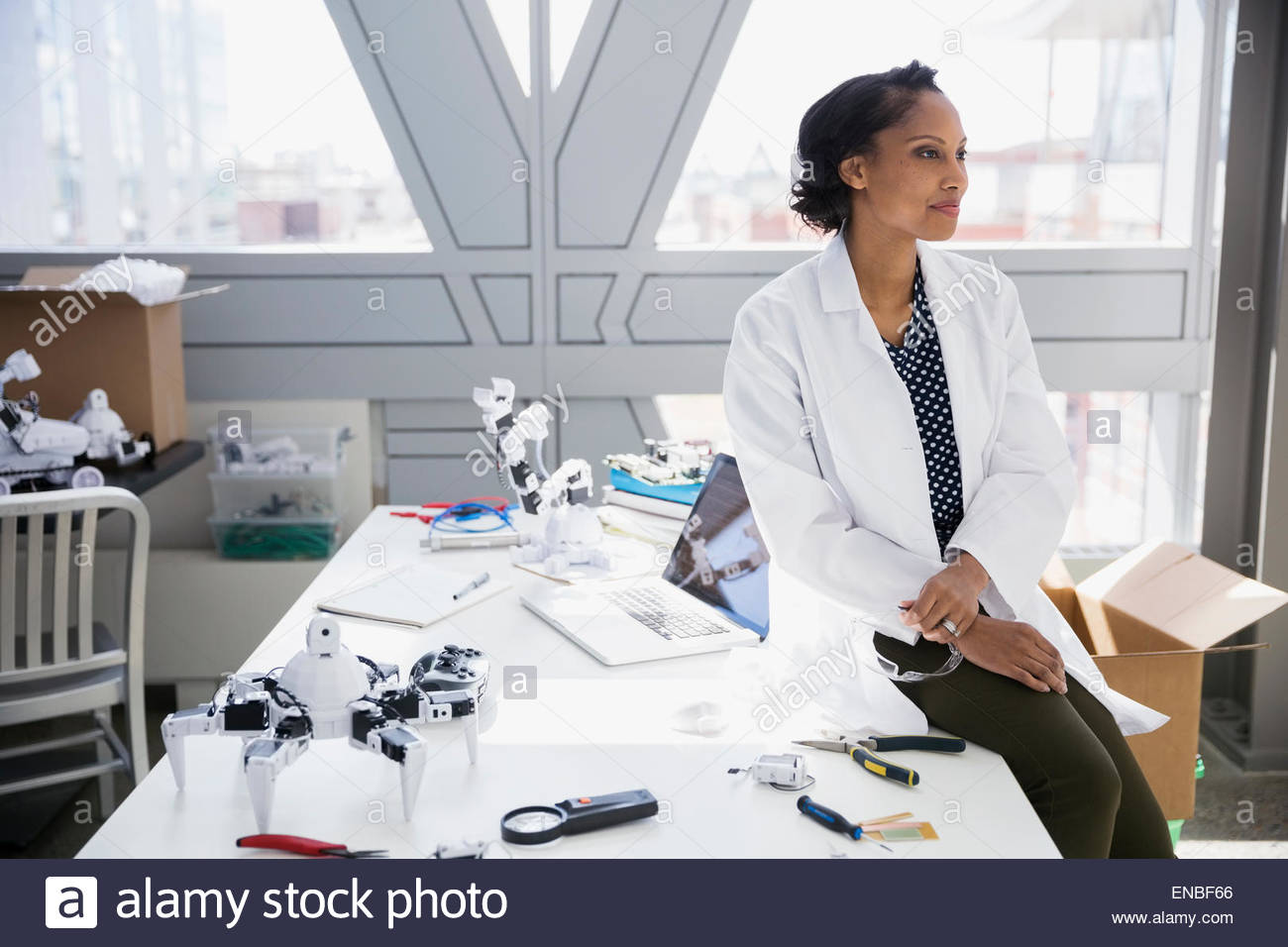 Pensive engineer at desk with robots - Stock Image